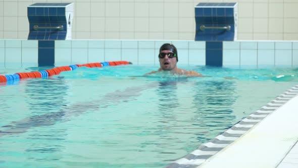 Thumbnail for Ein professioneller Schwimmer schwimmt die Brust in einem Hallenbad