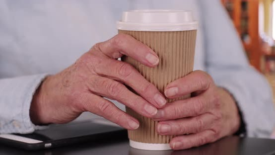 Close up of elderly lady's hands grabbing coffee cup in indoor kitchen setting