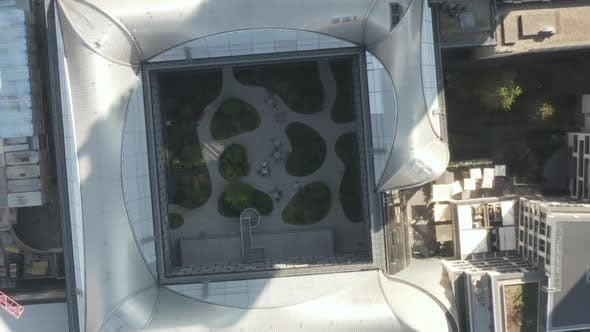 Thumbnail for AERIAL: Bird View of Skyscraper Garden with Green Trees in Urban Environment with City Car Traffic