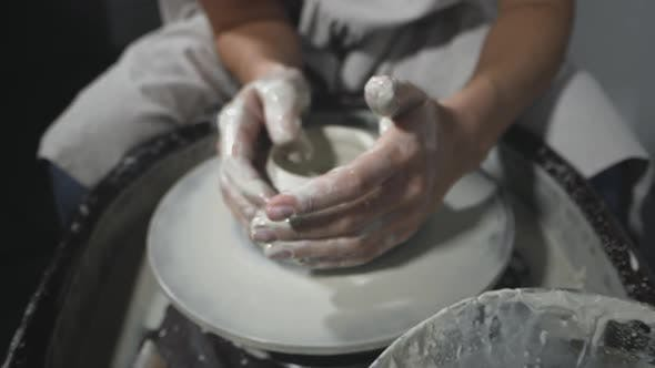 Thumbnail for Potter molds clay pot on potter's wheel in workshop