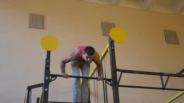 Young Athlete Doing Handstand on Horizontal Bar at Gym