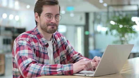 Serious Male Designer with Laptop Saying No By Head Shake