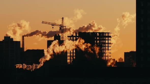 Cover Image for Silhouette of Tower Crane Working on Construction Site Residential Building Sunrise or Sunset Light
