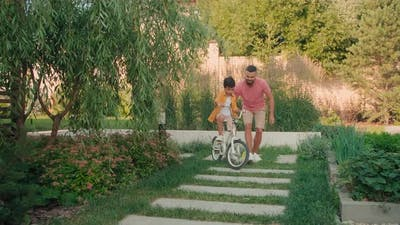 Dad Teaching Son To Ride Bicycle In Backyard