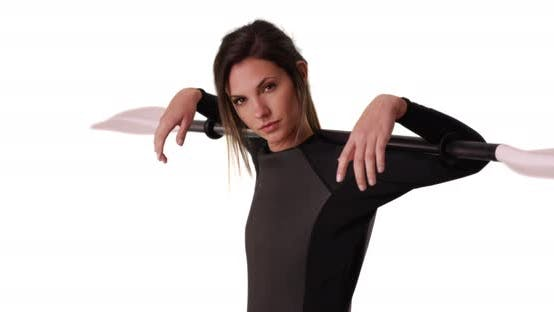 Thumbnail for Young woman in wetsuit holding kayak paddle over shoulders on white background