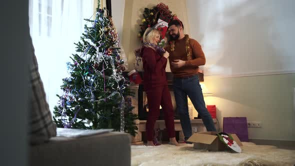Thumbnail for Young Bearded Caucasian Man Hanging New Year Decoration on Blond Beautiful Woman. Wife Kissing Her