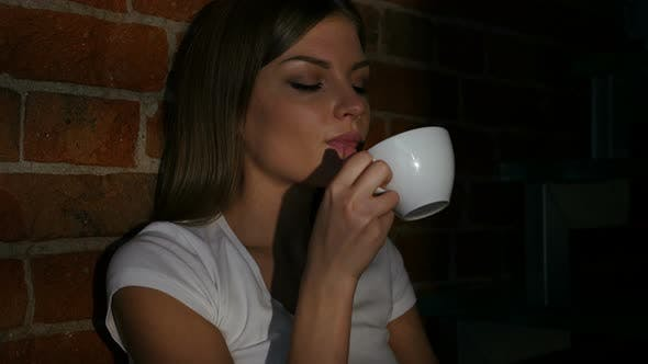 Thumbnail for Pensive Young Woman Drinking Coffee from Cup at Night