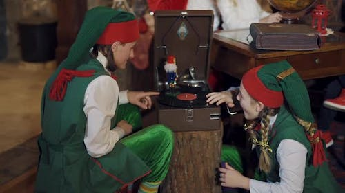 Funny elves in fairy costumes play with a toy indoors. Two elves male and female spinning
