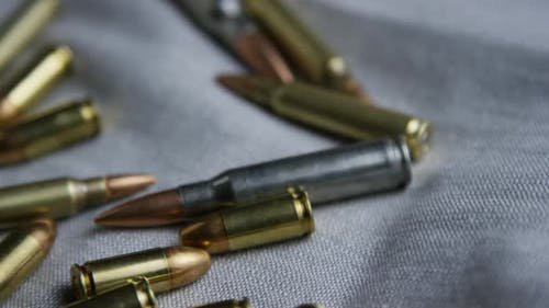 Cinematic rotating shot of bullets on a fabric surface - BULLETS 097