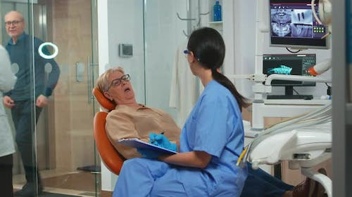 Patient with Tooth Pain Explaining Dental Problem to Nurse