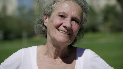 Cheerful Grey Haired Old Lady Posing in City Park