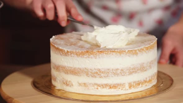 Female Cook Applies Cream on the Top Layer