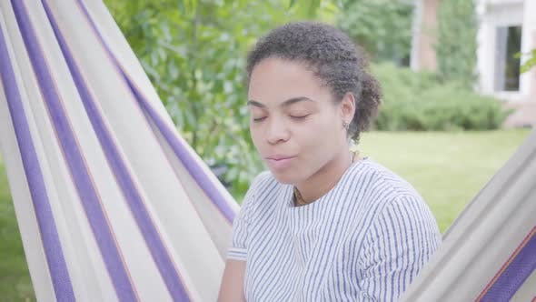 Thumbnail for Portrait of Cute Young Smiling African American Woman Sitting in the Hammock, Relaxing in the Garden