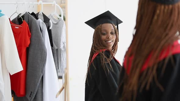 African Woman Trying on Fitting Cap and Gown and Looking in Mirror with Happy Smile Spbi