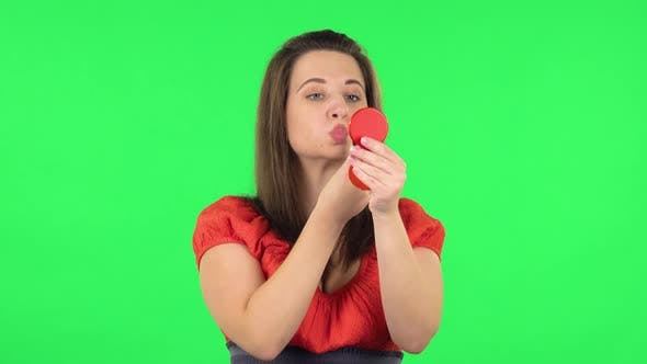 Thumbnail for Portrait of Cute Girl Is Painting Her Lips Looking in Red Mirror. Green Screen
