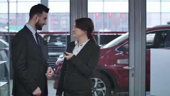Thumbnail for Porträt von aufgeregt kaukasische Frau immer Schlüssel aus neuen roten Auto von männlichen Händler und machen