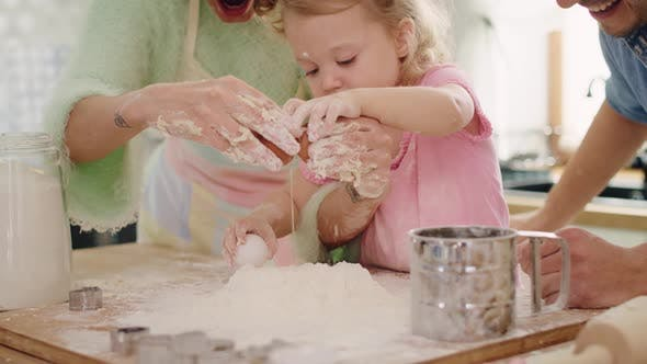 Thumbnail for Handheld view of little girl making cookies with parents. Shot with RED helium camera in 8K