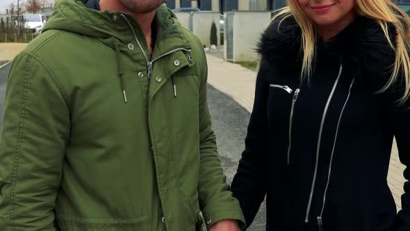 Thumbnail for A Young, Attractive Couple Holds Hands, Smiles at the Camera and Eventually Looks on an Empty Street