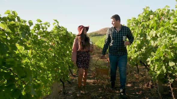 Thumbnail for Beautiful Couple with Glasses of Wine in Hands and a Basket of Grapes
