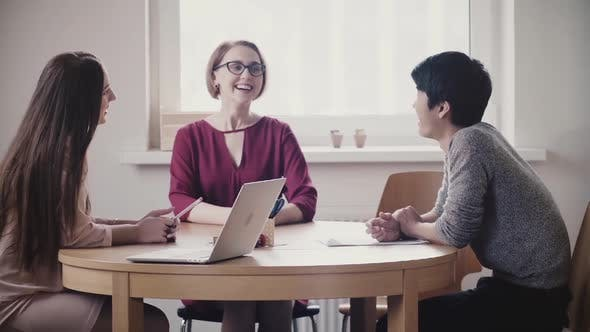 Thumbnail for Two Beautiful Positive Caucasian Girls Talk To Japanese Man at a Job Interview By the Table