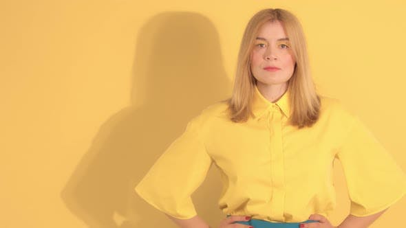 Thumbnail for Young Woman in Bright Clothes on Bright Yellow Background in Studio