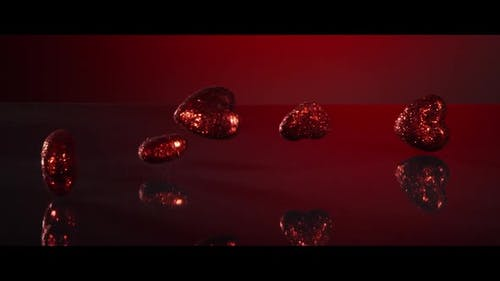 Valentine's Day decorations falling and bouncing on a reflective surface - VALENTINES