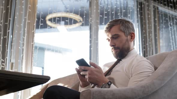 Cover Image for Businessman Using Phone in Café