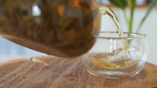 Tee Gießen. Tee wird in Glas transparente Teetasse gegossen. Tee-Zeit. Transparente Glas-Teekanne und