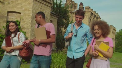 Multiracial Group of Cheerful Students Walking and Laughing Outdoors