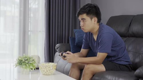 young man playing video game with joystick in the living room