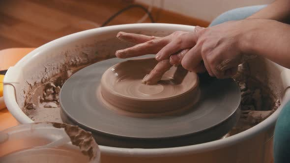 Cover Image for Pottery - Master with Finger Is Making the Bottom for a Clay Bowl on the Potter's Wheel