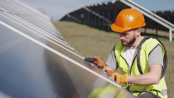 Thumbnail for Male Engineer in a Uniform Is Checking the Solar Battery Outside