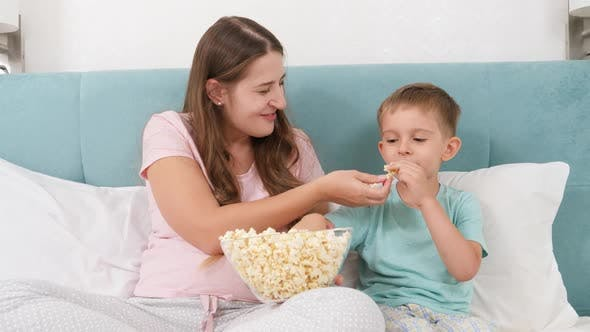 Thumbnail for Little Toddler Boy with Young Mother in Pajamas Lying in Bed on Weekend and Eating Popcorn From Big
