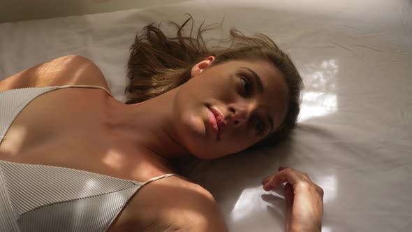 Brown-Haired Woman on White Sheets Relaxing