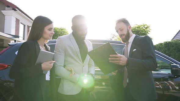 Thumbnail for African Man and European Woman in Formal Wears Talking with Car Dealer About Buying New Car