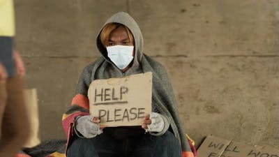 Homeless man holding help please label