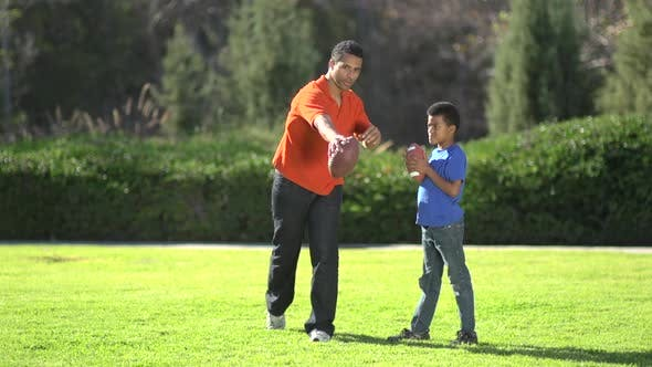 Thumbnail for A father teaching his sons how to play American football.