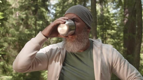 Porträt des gealterten Wanderer trinken Tee im Wald