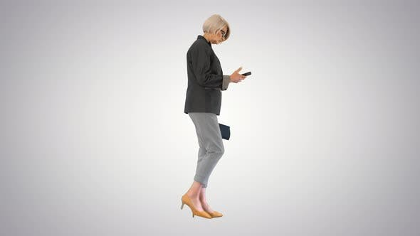 Elegant Senior Woman Using Smartphone While Walking on Gradient Background
