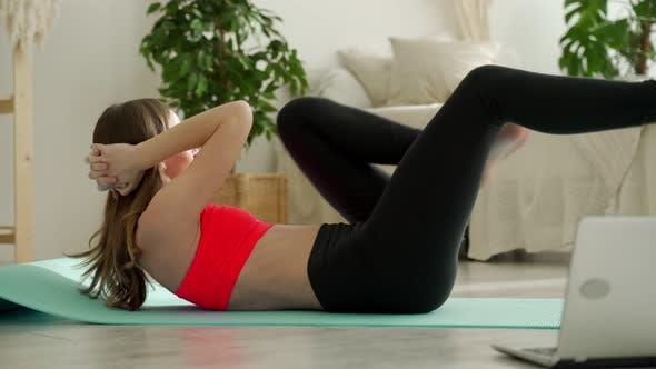 Athletic Woman Doing Abs in the Bedroom Next to a Laptop with an Online Workout