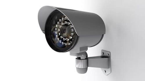 Sicherheits-CCTV-Kamera auf weißem Hintergrund dreht sich und überwacht Crowd