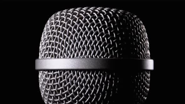 Thumbnail for The Microphone Rotates on a Black Background. Dynamic Microphone Grid Spins Close-up