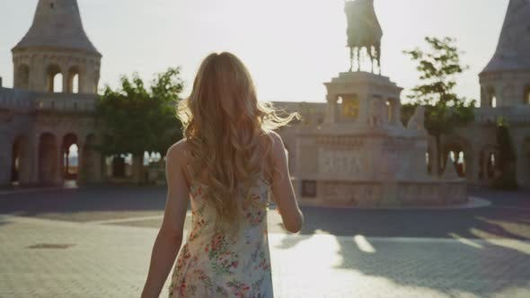 Thumbnail for Woman walking towards a statue