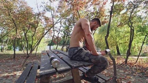 Muskulöser Bodybuilder pumpt seinen Arm Bizeps