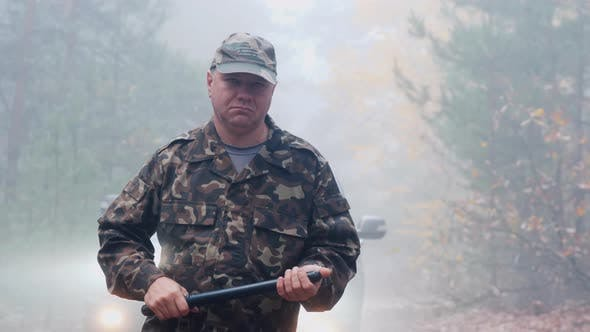 Thumbnail for Portrait of an Angry Security Guard in Camouflage Uniform with a Rubber Baton in His Hands