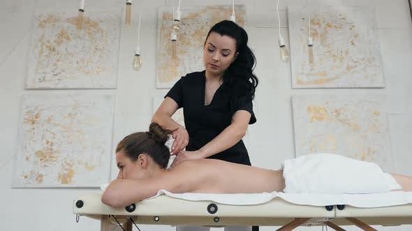 Thumbnail for Konzentrierte kaukasische Masseur machen entspannende Massage für junge Frau im Spa Salon