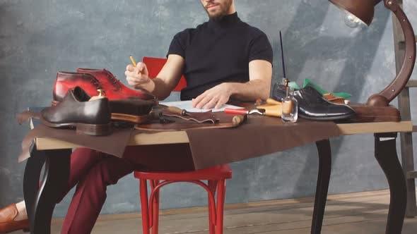 junge Schuster erkunden ein gemalt stiefel