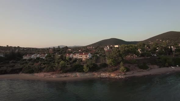 Thumbnail for - Aerial Scene of Trikorfo Beach Shore with Cottages and Green Hills, Greece