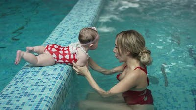 Mother Helps Her Little Daughter to Swim