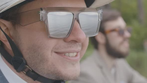 Thumbnail for Close-up Face of Confident Young Man in Sunglasses and Helmet Smiling in Slow Motion. Portrait of